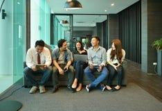 Travail d'équipe des gens d'affaires asiatiques s'asseyant sur le sofa dans le salon Image libre de droits