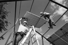 Travail d'équipe pour installer les pannels solaires innovateurs sur le toit photos libres de droits
