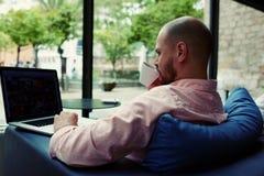 travail d'étudiant sur le thé potable de netbook ou le café noir tandis qu'il s'asseyant dans l'intérieur moderne d'hôtel Photos stock