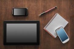 Travail d'affaires avec la Tablette, 2 Smartphones et un bloc-notes Photographie stock libre de droits