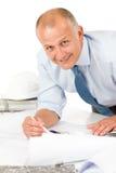 Travail d'homme aîné sur des plans de construction de modèles Images libres de droits