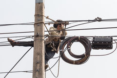 Travail d'homme d'électricien sur le poteau électrique Images stock