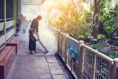 Travail d'homme embrumant pour éliminer le moustique pour empêcher le virus écarté de fièvre dengue et de zika Photographie stock libre de droits