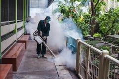 Travail d'homme embrumant pour éliminer le moustique pour empêcher le virus écarté de fièvre dengue et de zika Image libre de droits