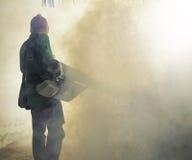 Travail d'homme embrumant pour éliminer le moustique pour empêcher le repaire écarté Image libre de droits