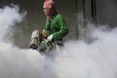 Travail d'homme embrumant pour éliminer le moustique pour empêcher le repaire écarté Images libres de droits