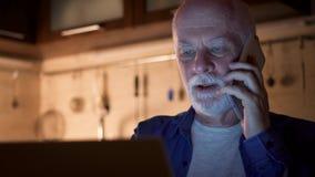 Travail d'homme supérieur sur l'ordinateur portable du siège social dans la soirée Entretien d'indépendant au téléphone portable  banque de vidéos