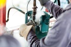 Travail d'homme un réservoir de propane Photo stock