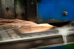 Travail d'une machine industrielle de rectification superficielle Meulage d'une pièce plate en métal photos stock