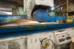 Travail d'une machine industrielle de rectification superficielle Meulage d'une pièce plate en métal photo stock