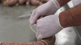 Travail d'usine de viande Le travailleur de sexe masculin attache la viande avec le filet Procédé de fabrication de saucisse banque de vidéos
