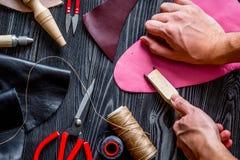 Travail dans la boutique en cuir sur la vue supérieure de fond en bois foncé image stock