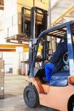 Travail de chargeur de chariot élévateur d'entrepôt images stock