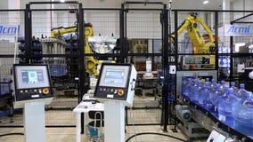 Travail de chargeurs de robots dans un entrepôt Bouteilles d'eau pures passant le convoyeur banque de vidéos