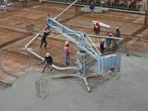 Travail de Concreting ? c?t? des travailleurs de la construction au chantier de construction images libres de droits