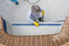 Travail de détail sur la nouvelle tuile d'amd de plâtre de piscine Photographie stock libre de droits
