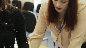 Travail de deux femmes dans le bureau l'un à côté de l'autre banque de vidéos