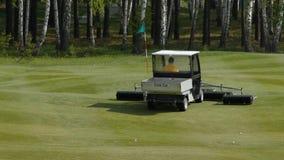 Travail de faucheuse dans l'herbe au bord d'un terrain de golf écossais Machine pour le gazon sur le golf photographie stock libre de droits