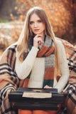 Travail de femme d'auteur sur la vieille machine à écrire en parc d'automne photos stock