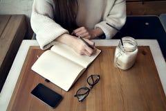 Travail de femme en café, bloc-notes dans un restaurant près de temps de déjeuner de fenêtre avec du café Photographie stock