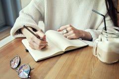 Travail de femme en café, bloc-notes dans un restaurant près de temps de déjeuner de fenêtre avec du café Images stock