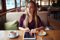 Travail de femme sur le PC de comprimé utilisant le wifi en café photos libres de droits