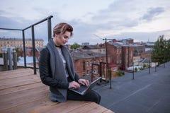 Travail de fille sur l'ordinateur portable sur le toit Photographie stock