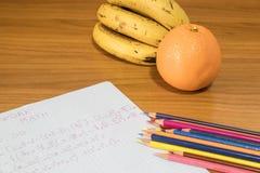 Travail de maths avec des crayons et des bananes et fruit orange Photos libres de droits