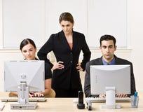 Travail de observation de collègues de femme d'affaires Images stock