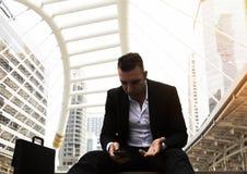 Travail de pensée d'homme d'affaires et regardant la tristesse de dispositif de téléphone portable puis images stock