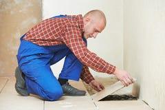 Travail de rénovation de carrelage de plancher de carreleur à la maison images libres de droits