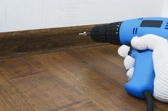 Travail de réparation d'intérieur Homme vissant un boulon Fixation des conseils de skirtings à l'aide d'instrument spécial photographie stock