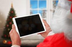 Travail de Santa Claus sur le comprimé avec l'écran vide pour la maquette Photographie stock libre de droits