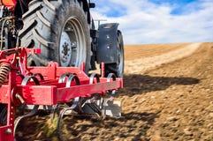 Travail de tracteur dans le domaine Roues de tracteur et haut étroit d'équipement photos stock