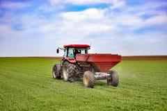 Travail de tracteur sur le champ Appliquant l'engrais au printemps photos stock
