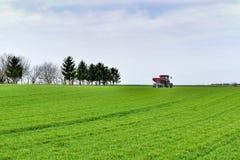 Travail de tracteur sur le champ Appliquant l'engrais au printemps photos libres de droits
