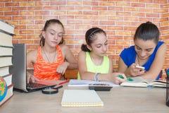 Travail de trois filles sur son travail Portrait de l'étude d'étudiant d'école de trois filles image stock