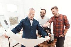 Travail de trois ingénieurs avec une imprimante 3d Un homme plus âgé dans le premier plan étudie un modèle Images libres de droits