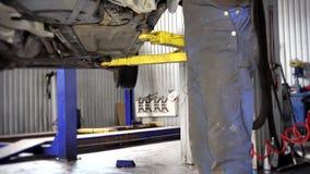 Travail de type de mécanicien automobile sur le circuit de freinage de voiture Inclinaison  banque de vidéos
