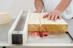 Travail du bois, un homme coupant un conseil sur une machine circulaire de scie photographie stock