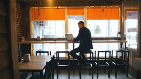 Travail du café Jeune homme gai dans la tenue de détente futée regardant l'ordinateur portable et se reposant près de la fenêtre  clips vidéos