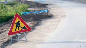 Travail en cours de panneau routier de triangle sur une rue sous la reconstruction Image stock