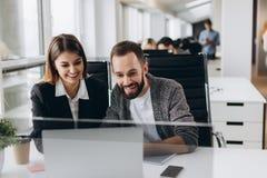 Travail ensemble sur le projet Deux jeunes collègues d'affaires travaillant sur l'ordinateur photographie stock libre de droits