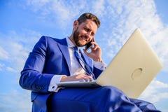 Travail formel de costume d'homme avec l'ordinateur portable tandis que parlez du téléphone Guide final de chef devenant de vente photos stock