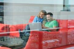 Travail heureux de couples sur l'ordinateur portatif à la maison Photo libre de droits