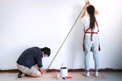 Travail intérieur, peintre deux avec la bande de mesure vérifiant le mur le photographie stock libre de droits