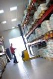 Travail jaune de poussoir de fourchette dans le grand entrepôt. Dans la tache floue. Photo libre de droits