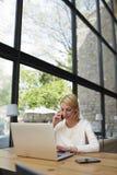 Travail occupé de jeune femme d'affaires réussie dans l'intérieur moderne de bureau de grenier utilisant des instruments de techn Photo stock