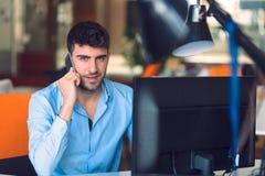 Travail occupé de jeune homme d'affaires sur l'ordinateur portable tout en parlant sur le Smart-téléphone au bureau Image stock