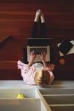 Travail occupé de jeune indépendant féminin sur l'ordinateur portable tout en se penchant sur la maison Photo libre de droits